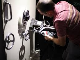 Man drilling into safe in order to unlock it